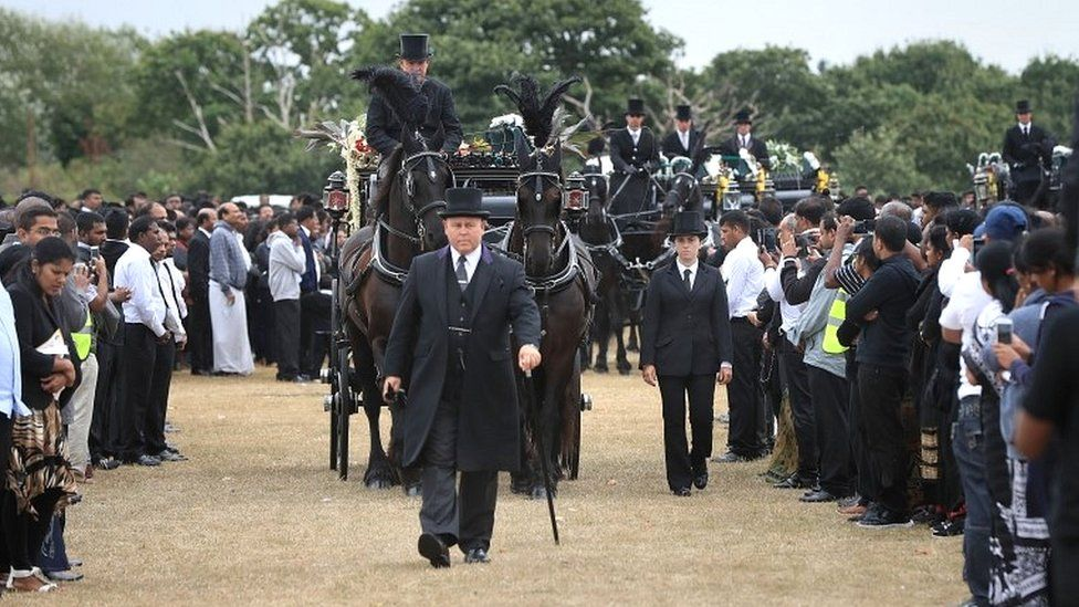 Five coffins are taken by horse drawn carriages to the crematorium after the funeral on Winn's Common Park