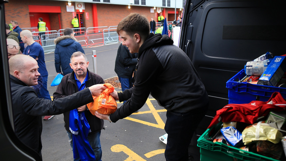 Fans donate food to a foodbank outside the ground ahead of the Premier League match between Liverpool and Everton