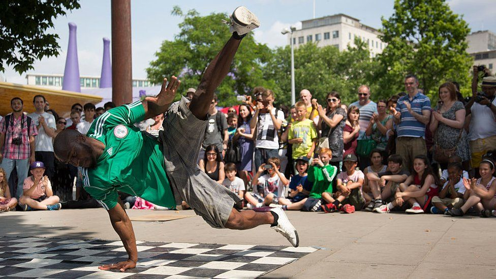 Break dance group One Motion Crew perform for money to a busy crowd of tourists on the South Bank, London