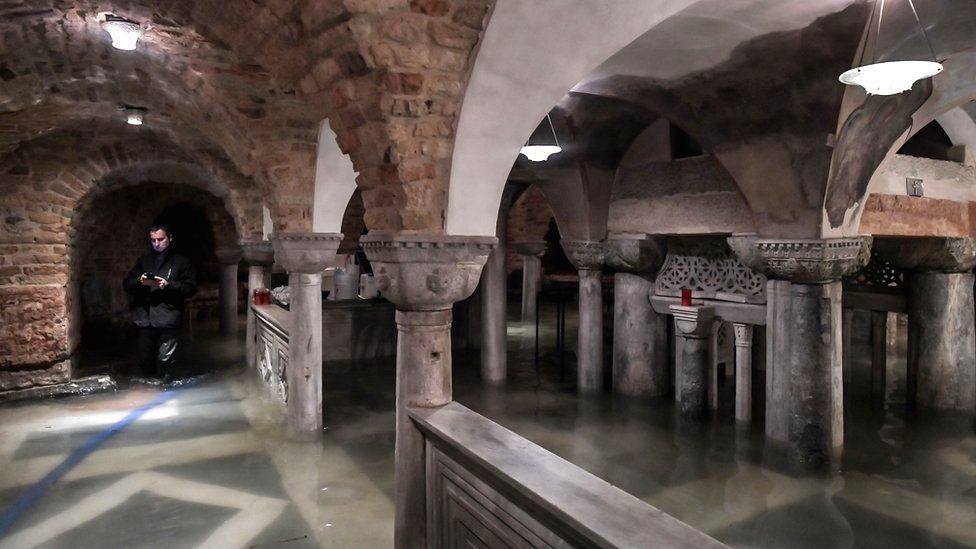 A man pumps water from the flooded crypt of St Mark's Basilica in Venice, 13 November 2019