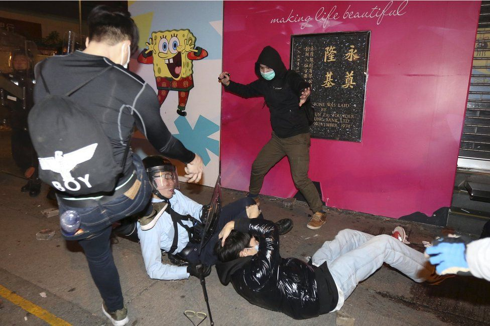 A rioter attacks a police officer on the ground
