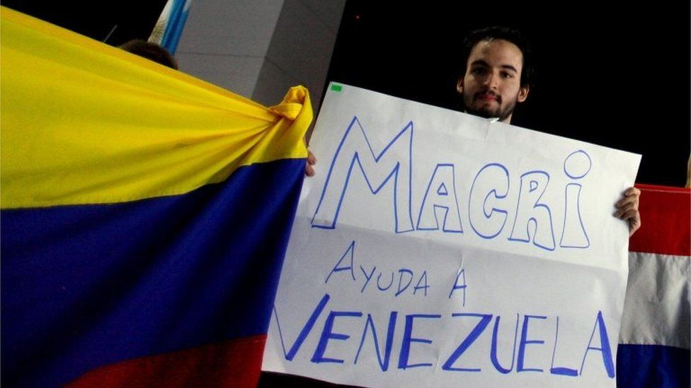"Venezuelan citizen Angel Sosa holds up a sign that reads ""Macri, help Venezuela"" in front of the Obelisk of Buenos Aires, on 22 November, 2015."