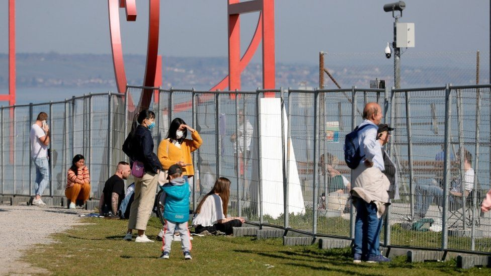 People meet for a chat at the closed border to Switzerland, in Constance, Germany, 06 April 2020