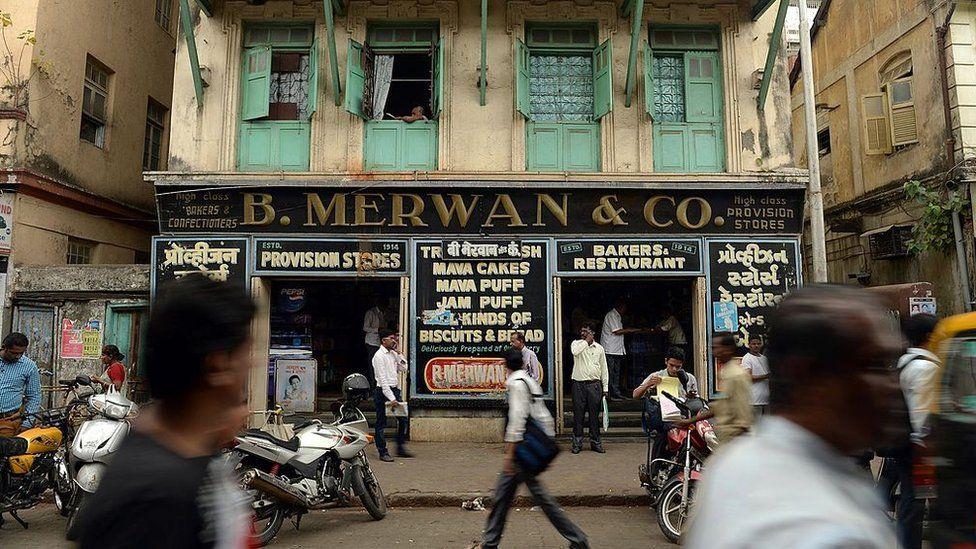 Indian pedestrians walk past the B. Merwan & Co. Irani cafe in Mumbai