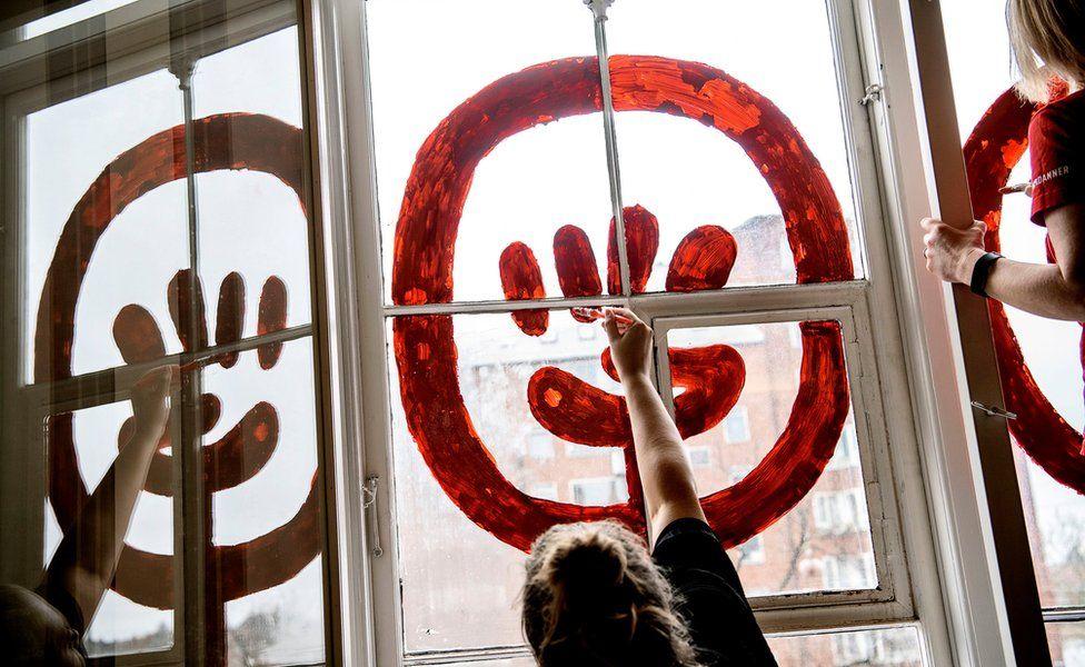Women painting windows for International Women's Day in Copenhagen