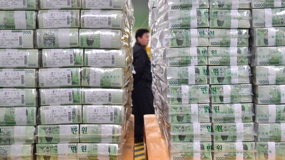 Bundles of South Korean bank notes for release are stacked as a security worker is seen in the basement of the central bank in Seoul.
