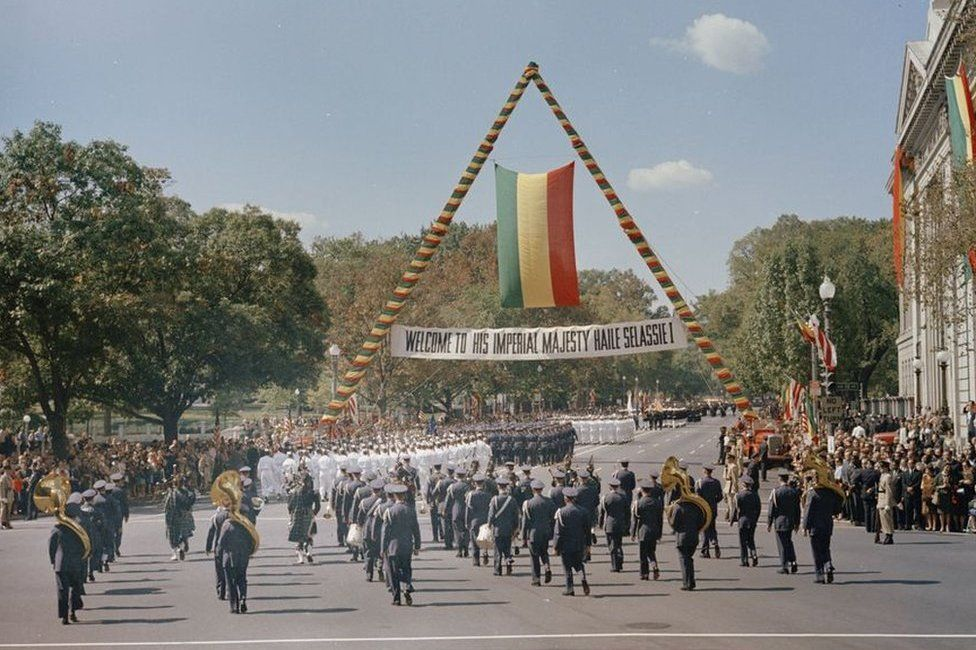 Crowds under a banner welcoming Haile Selassie