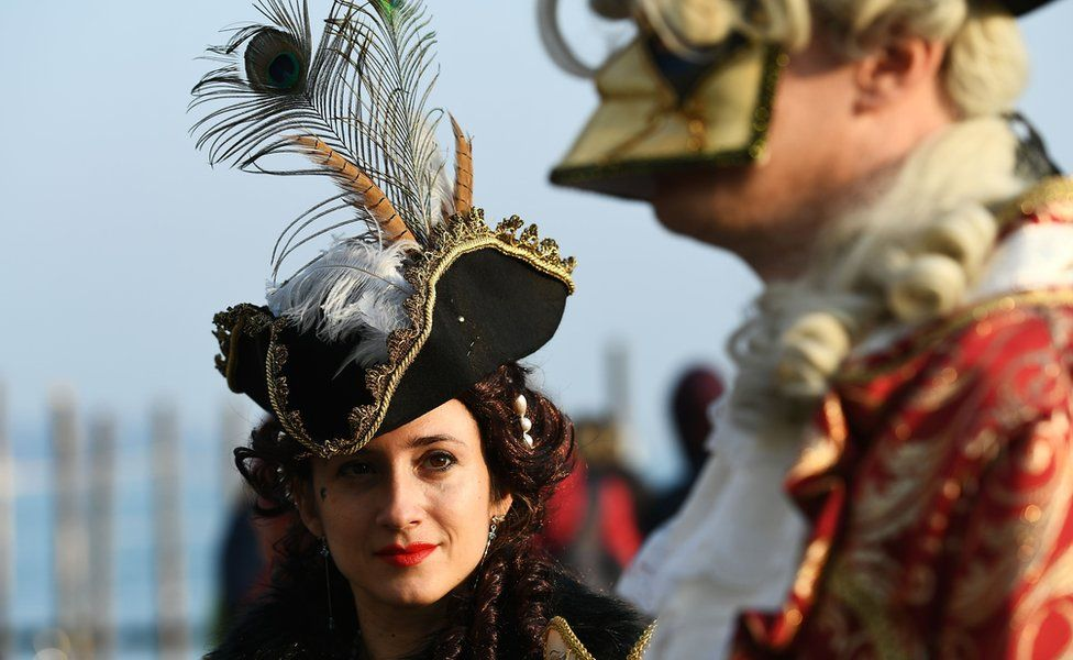 A woman looks at a masked man during the Venice carnival