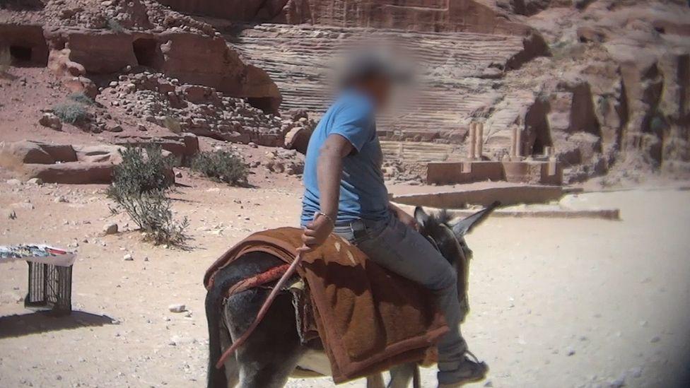 A man rides a donkey at Petra