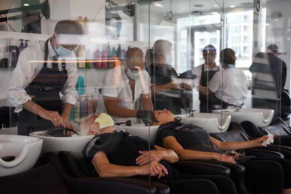 Women lean back to have their hair washed with plastic barriers dividing each customer