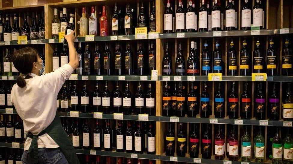 A shop worker grabs a bottle from the Australian wine section in a Beijing bottle shop