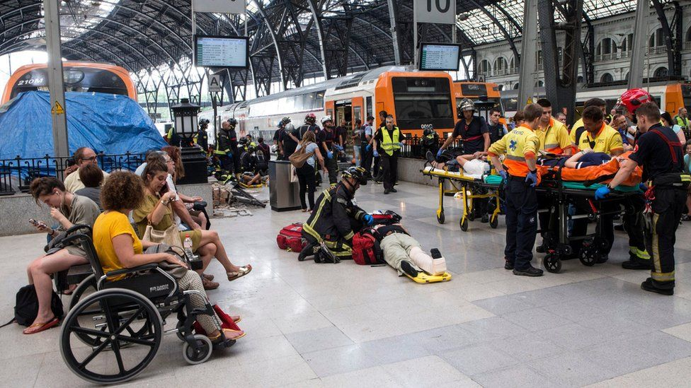 Spanish firefighters and paramedics treat injured people at Francia Railway Station in Barcelona, north-eastern Spain