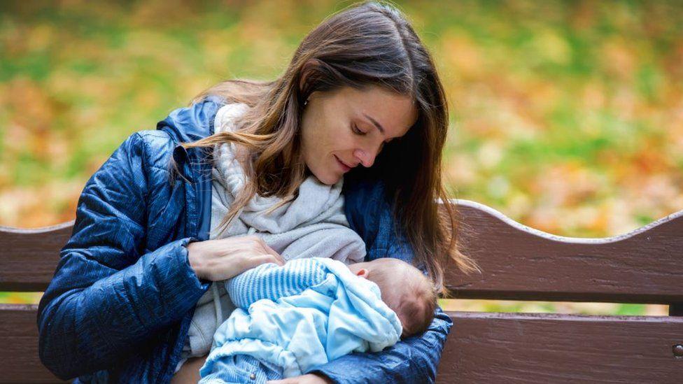 Woman breastfeeding in a park