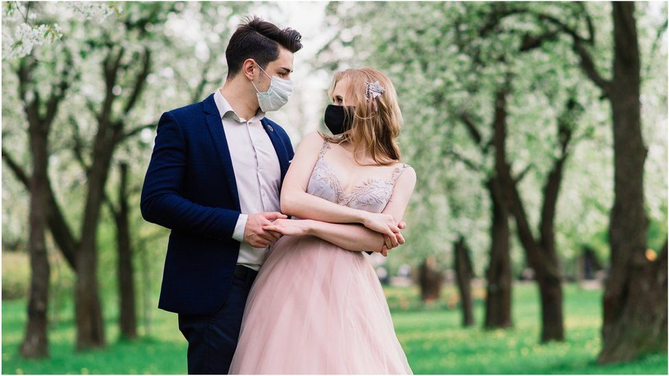 A bride and a groom with masks on