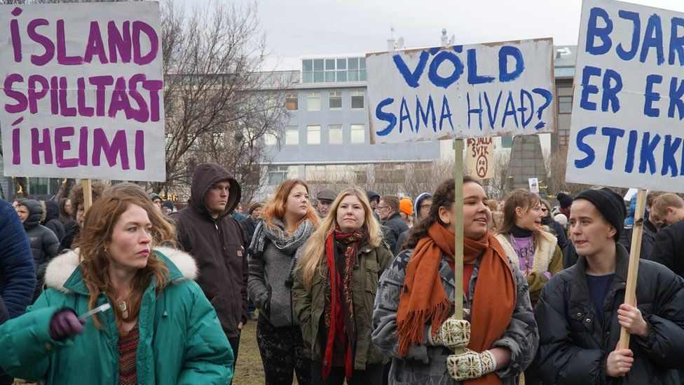 People hold banners and protest in front of Parliament building in Reykjavik