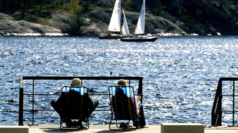 A Swedish couple on deck chairs overlooking the sea in Sweden