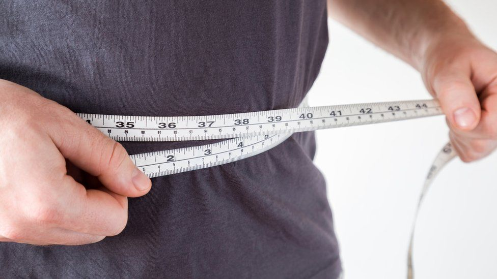 Person with measuring tape around waist