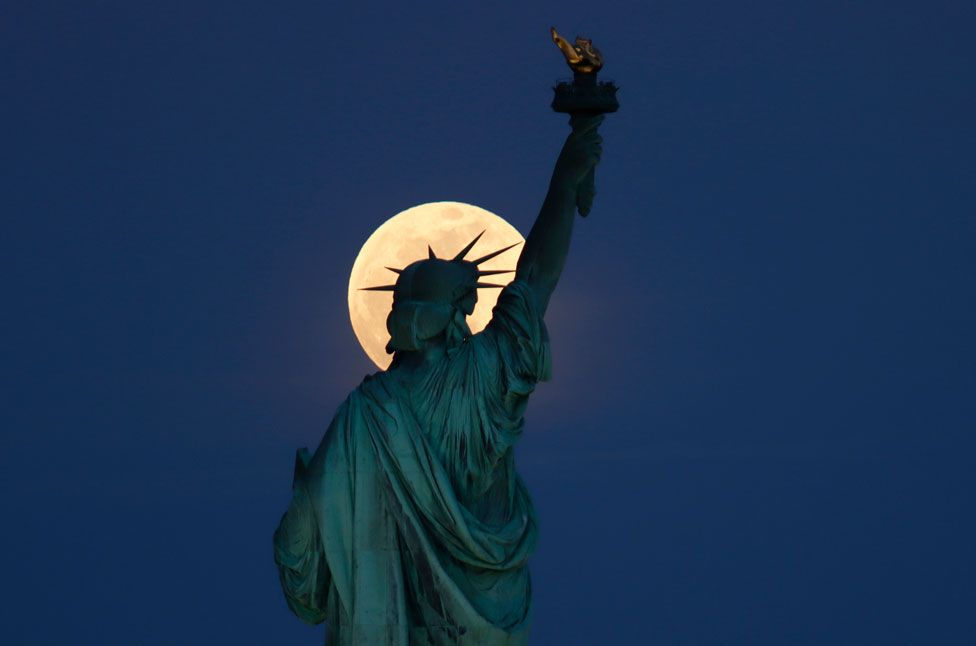 The Statue of Liberty in New York City, US, seen with the rising supermoon in the sky