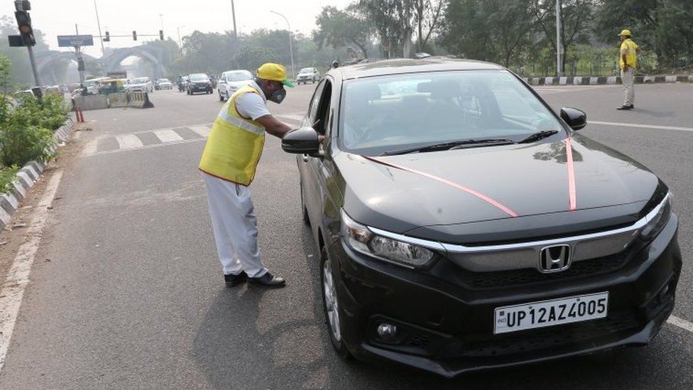 An odd number car is stopped by the civil defence volunteers during the first day of the implementation of the odd-even scheme