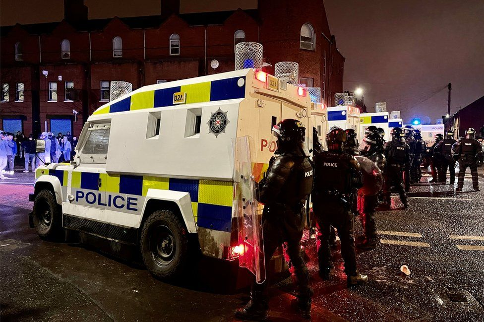 Police officers in riot gear stand behind armoured police Land Rovers