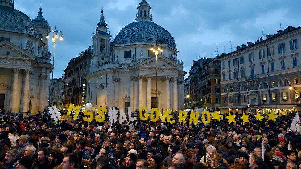 """A large crowd gathers in a city square. Among them are individual letters arranged to say : """"M5S al governo *****"""""""