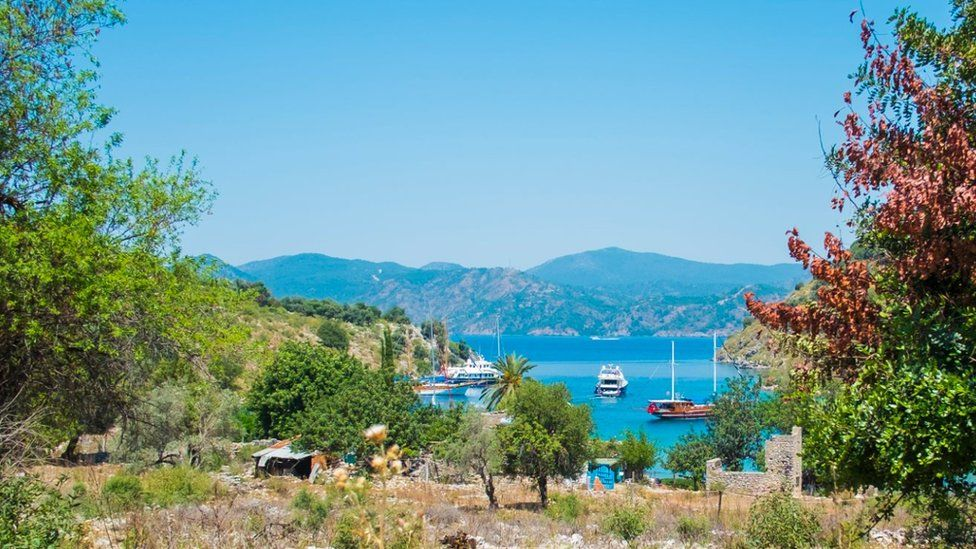 Panoramic view from an island to a bay with luxury yachts and sailing boats on May 25, 2014 in the Gulf of Fethiye, Lycian Coast, South of Turkey