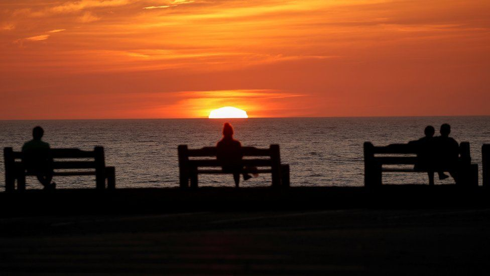 Two people sit on separate benches at sunset while a couple sit together on one bench