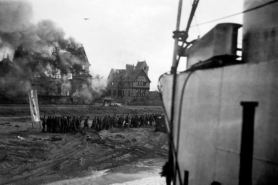 A German bomber in action on D-Day, as German prisoners are moved from Juno beach