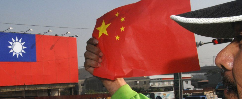 An anti-China protester holds the national flag of China during a demonstration outside of the Windsor hotel, where a fresh round of talks between Taiwan and China talks was being held in the central Taichung city on December 22, 2009. In the bacground was a huge national flag of Taiwan.