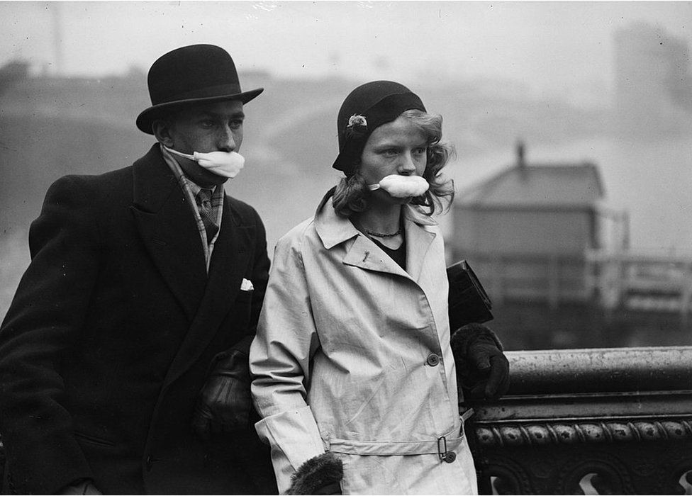Pedestrians in a London street wearing masks over their mouths