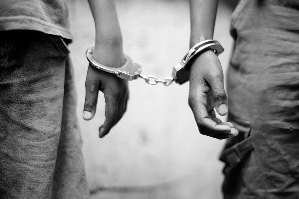 A close-up of kids wearing handcuffs