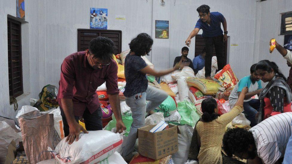 Volunteers handle and organise flood relief supplies