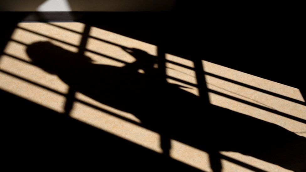 A shadow is cast of a cell door