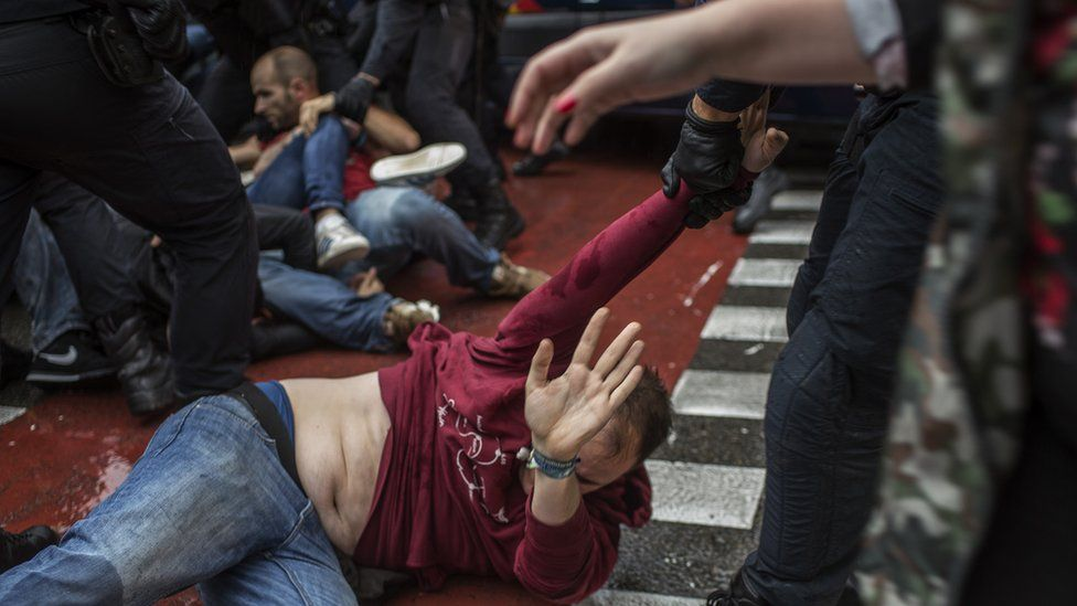 A man lying on the floor is dragged away by one arm, by a police officer.