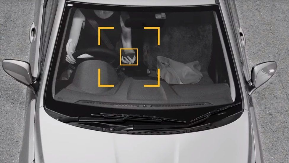 An illustration showing detection of a driver using their phone