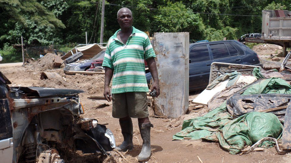 Ronald Jno Baptiste stands among the ruins of his car repair business in Jimmit