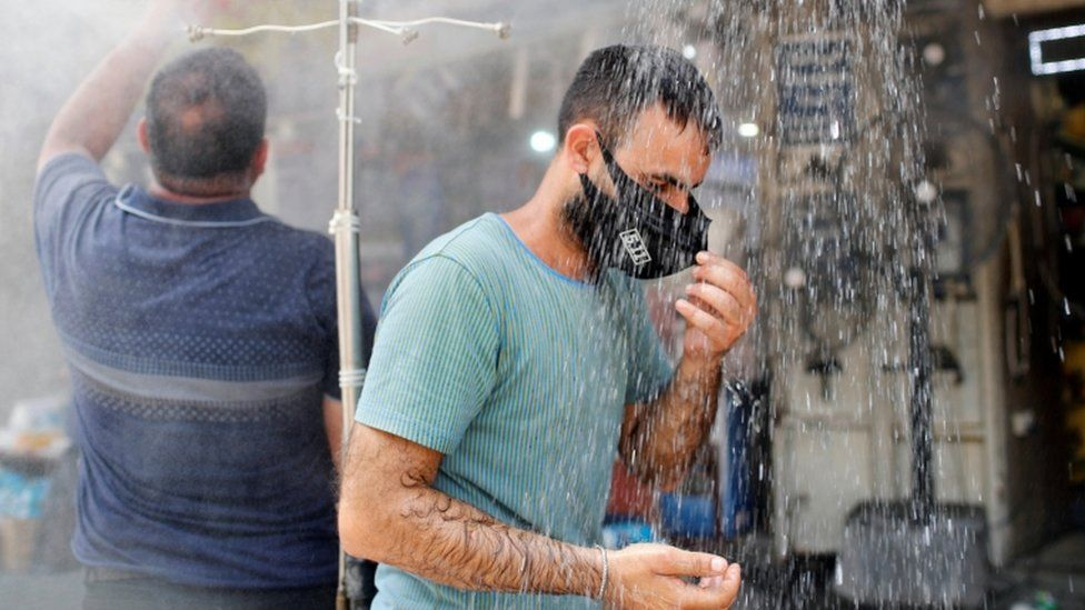 A man wearing a face mask stands under an outside shower in Baghdad on 28 July