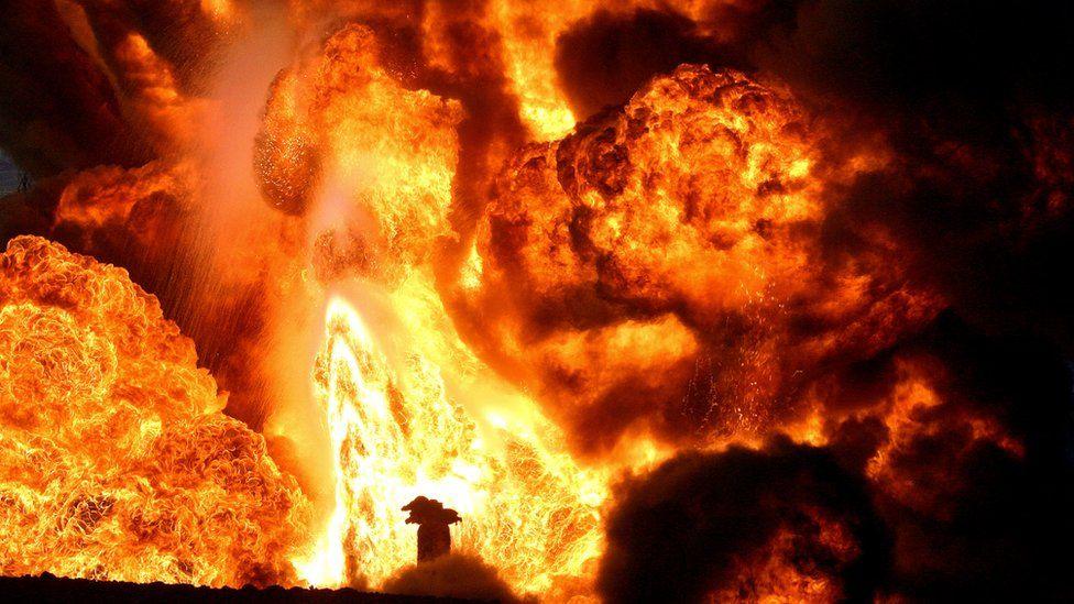 Oil fields sabotaged by insurgents in Iraq burn in 2005