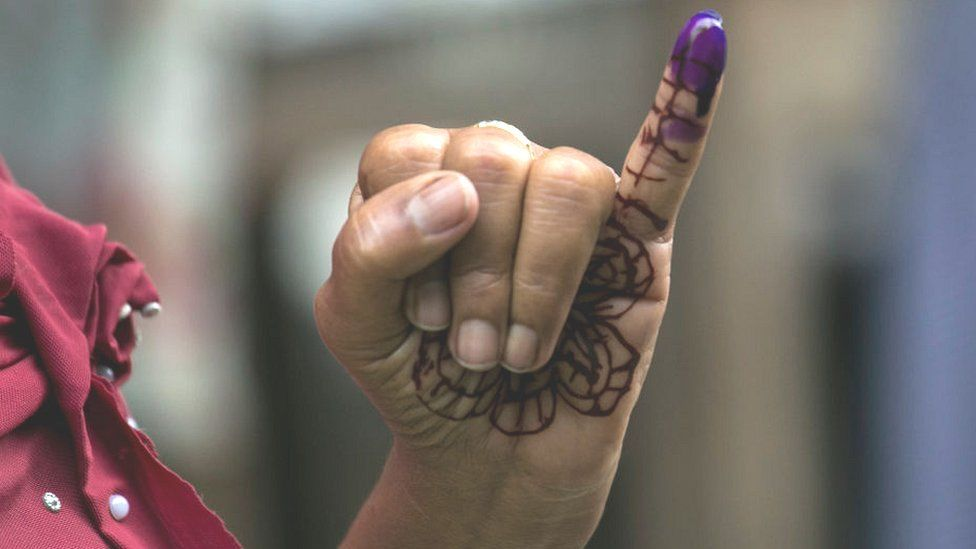 A woman holds up her inked finger after voting