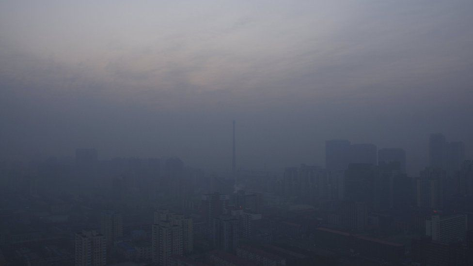 A chimney is seen near residential buildings amid heavy smog under a red alert for air pollution, in Beijing, China, December 19, 2015.