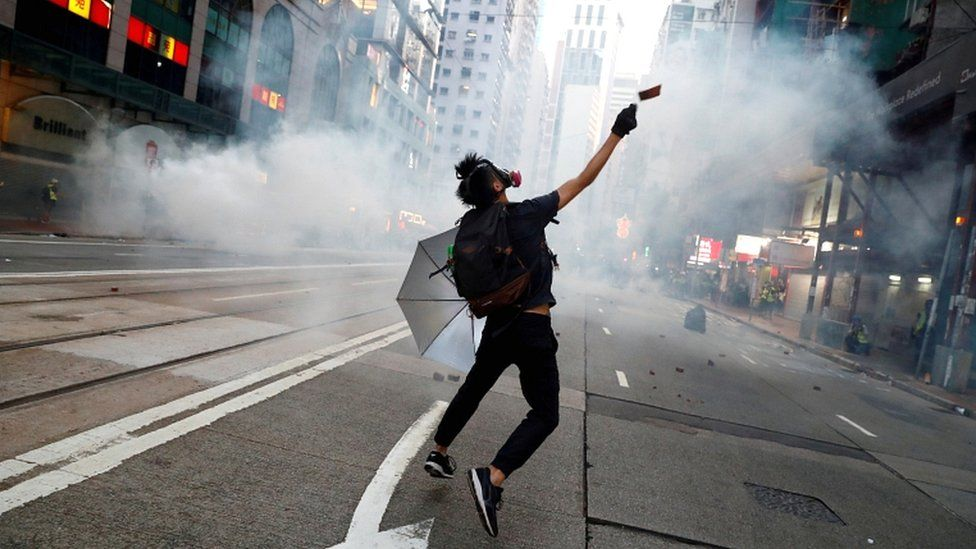 An anti-government protester reacts as police fire tear gas during a march billed as a global
