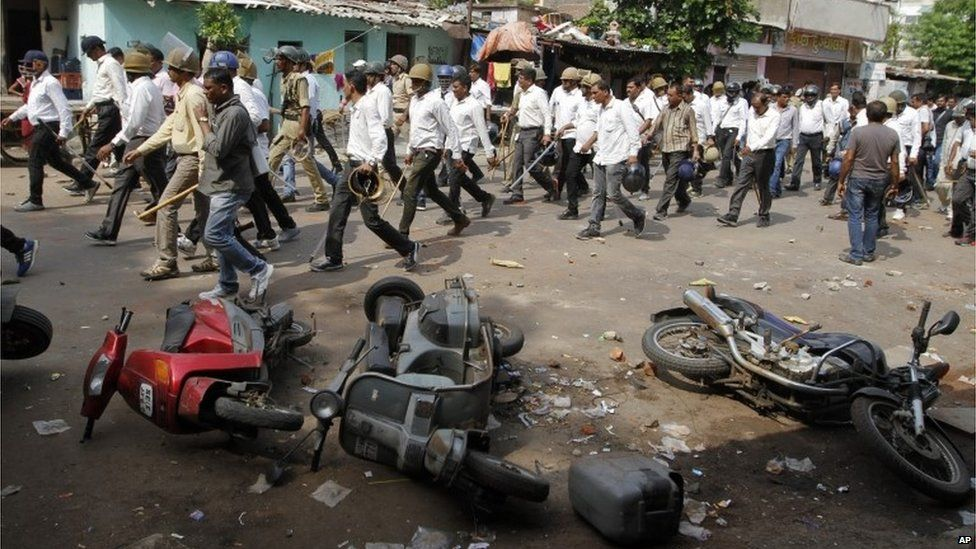Indian policemen in plain clothes walk past vehicles damaged during a clash between two groups in Ahmadabad, India, Tuesday, Aug. 25, 2015.