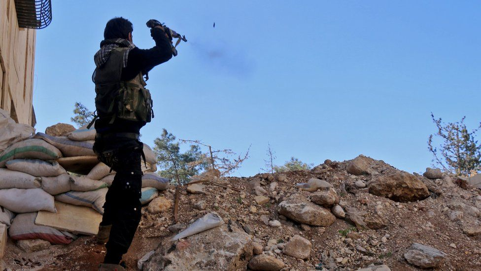 A rebel fighter fires towards pro-government positions, west of the northern Syrian city of Aleppo, 9 December