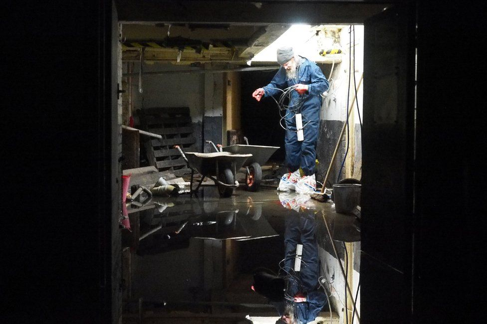 A man in a darkened room with a flooded floor