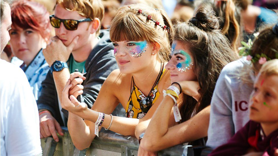Female festival goers in a crowd wearing glitter on their faces.