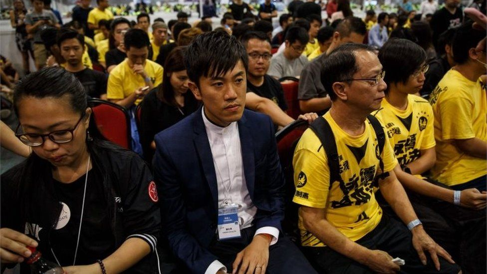 Civic Passion's Cheng Chung-tai (centre L) sits with supporters following his win in the Legislative Council election, at the central counting station in Hong Kong on September 5, 2016.