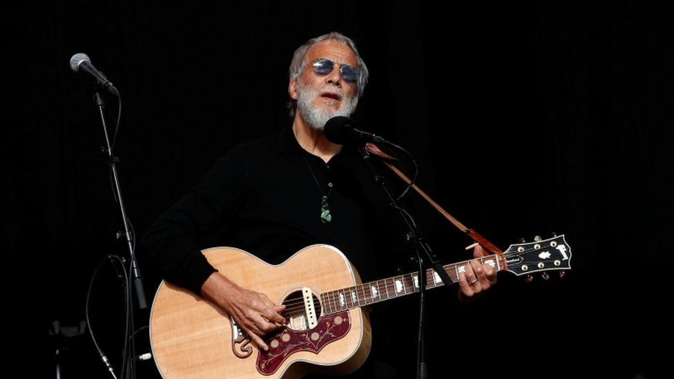 Cat Stevens playing guitar on stage at a memorial service for victims of the shooting on 29 March