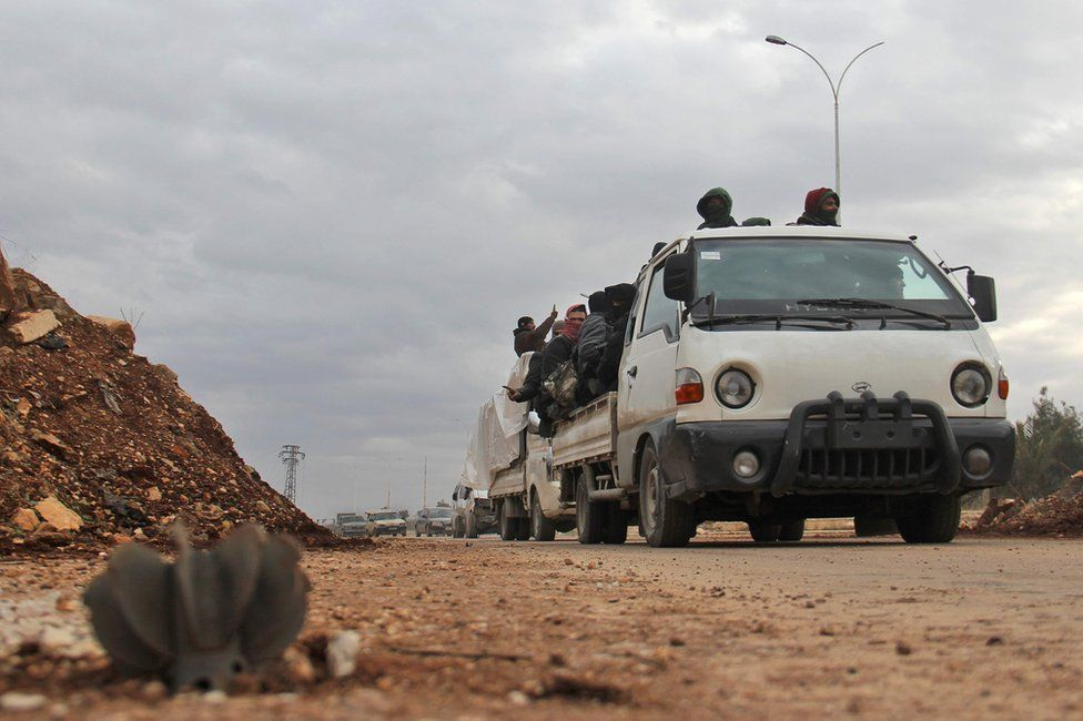 Aleppo evacuees pass an unexploded mortar round in the opposition-controlled Khan al-Aassal region, 16 December