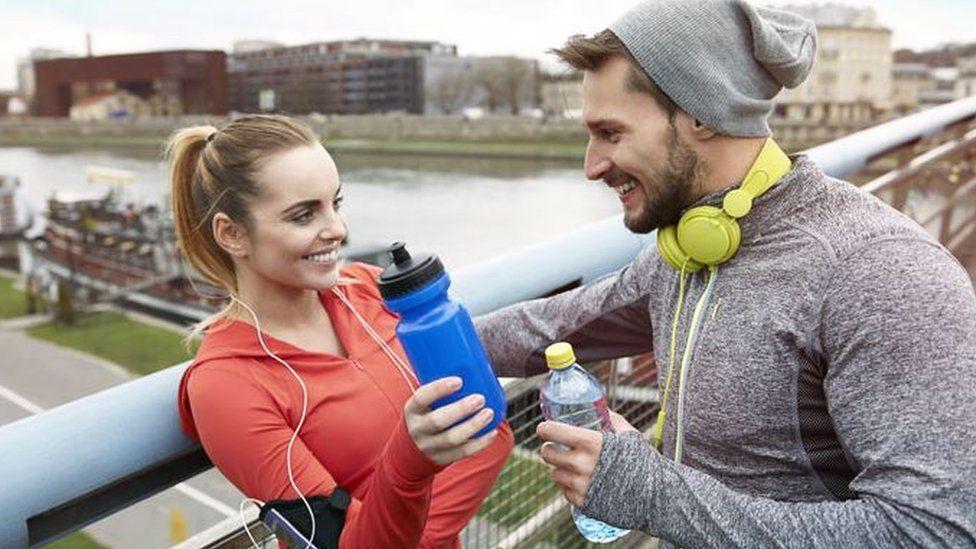 Screengrab of man talking to woman who has taken off her headphone