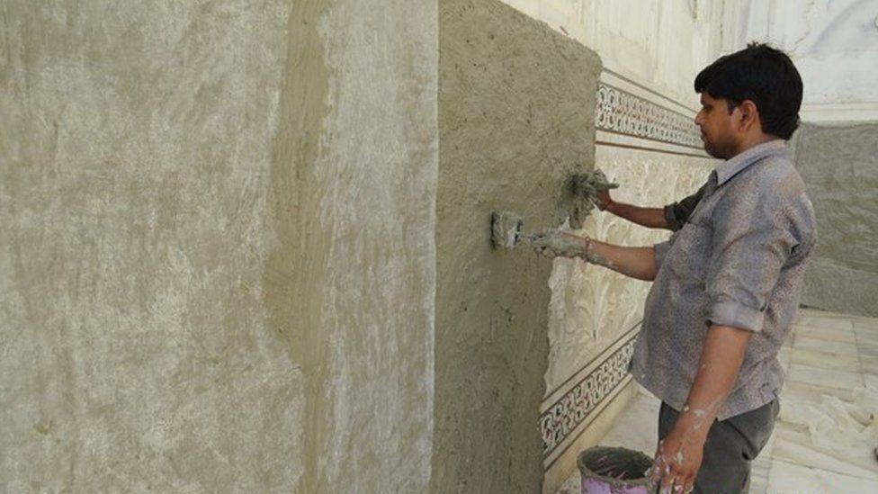"Men apply a ""mud pack"" onto the Taj Mahal"